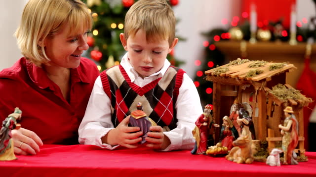 Mother and son set up Christmas nativity scene video