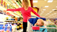 Mother and son shopping in a supermarket video