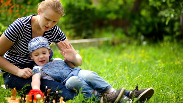 Mother and son spending time on the lawn in countryside video