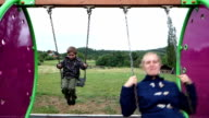 Mother and son swaying happily on a swing video
