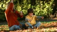 Mother and son throwing Fall leaves together video