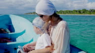 Mother and son using pad while traveling by sea video