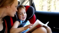 Mother and son with book traveling by car video