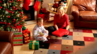 Mother and son wrapping gifts for Christmas video