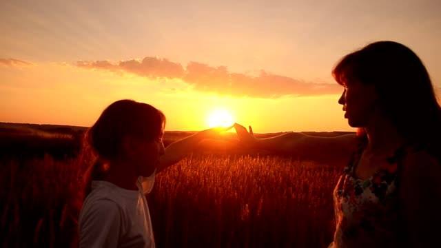 Mother and the daughter on a sunset video