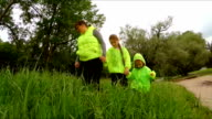 Mother And Two Children Walking In Green Gras In Park After Rain video