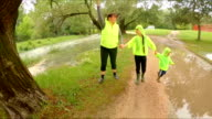 Mother And Two Children Walking In Park After Rain video