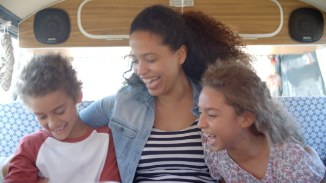 Mother and young children sitting in the back of camper van video