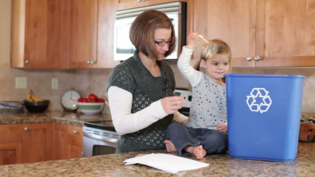 Mother and young daughter in kitchen recycling video