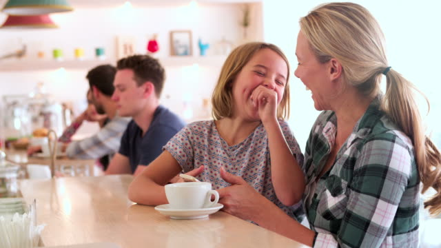 Mother and young daughter sitting at the counter in a cafe video