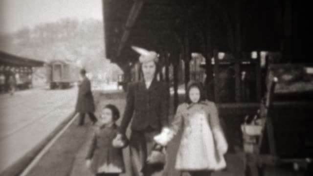 1941: Mother arrives at railroad train station holding daughters hands. video
