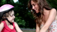 HD: Mother Assisting Daughter to ride a bike. video