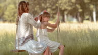 SLO MO Mother braiding daughters hair on a swing video