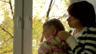 Mother braiding daughter's hair on the windowsill on a cloudy autumn day. video