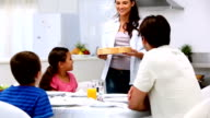 Mother bringing pizza to dinner table video