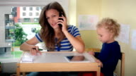 Mother call phone and help child girl play with tablet. Business woman work video