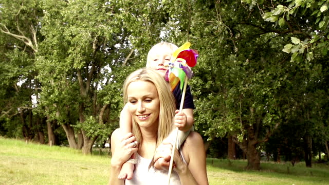 Mother carrying child with pinwheel video