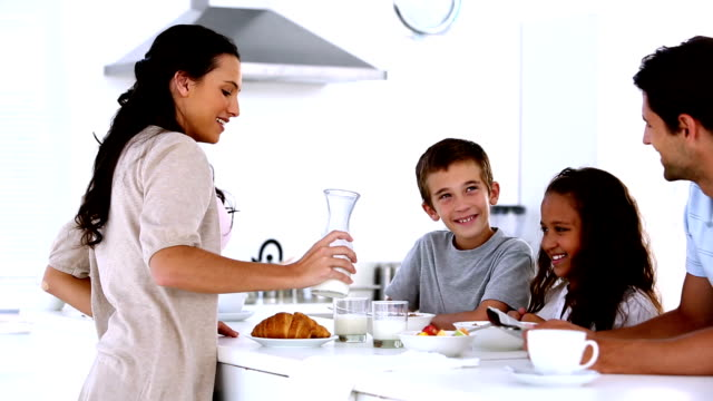 Mother chatting to children at family breakfast and pouring milk video