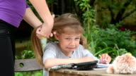 Mother combing daughter with long hair, which is very painful video