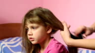 Mother combing her long hair girls and braid them into a pigtail video