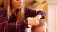 A mother doing her daughter's hair in the kitchen video