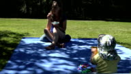 mother eat ice cream with satisfaction and cute baby play on plaid video