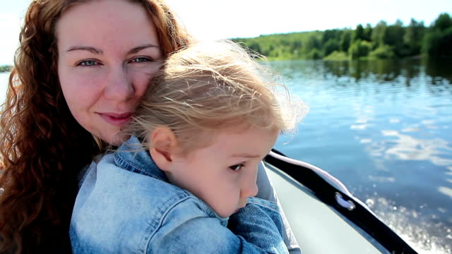 Mother embracing child in motor boat flying under lake video
