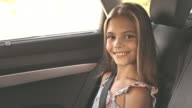 Mother fastening seat belt for young girl in the car video