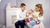 Mother, father and baby girl playing with money box video