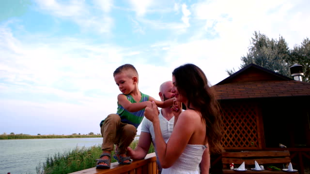 mother, father and son standing on a balcony, family on the terrace,overlooking the water, child kisses mother video