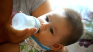 Mother feeding baby boy a bottle video