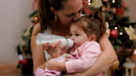 Mother feeding her cute baby girl with milk in a bottle on Christmas under the Christmas tree video