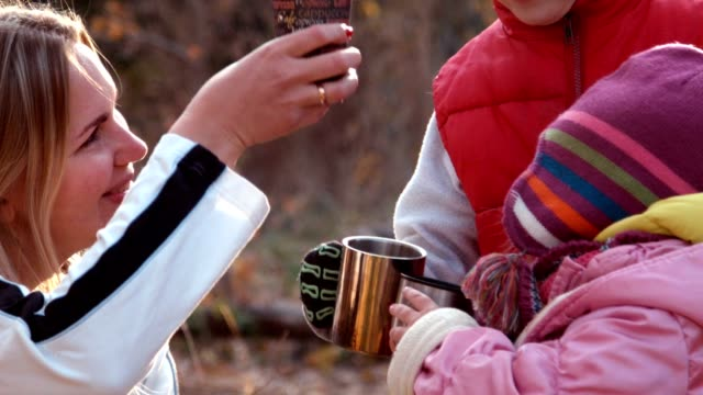 Mother gives some tea to children in autumn park video