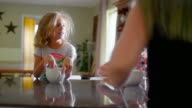A mother hands out large mugs to her daughters sitting at the kitchen counter video