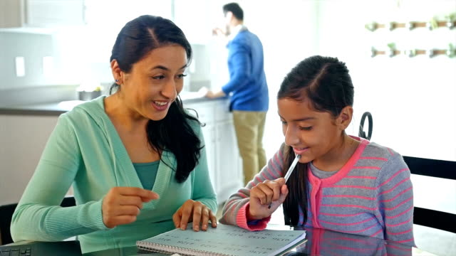 Mother helping her young daughter with math homework at kitchen table video