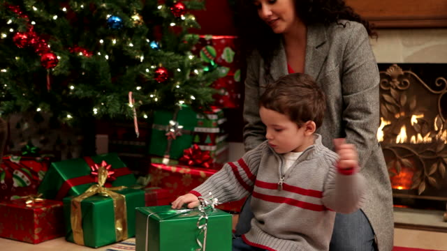 Mother helping son open Christmas gift video