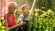 Mother helping son to water the garden with hose video