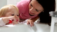Mother Helping Young Girl To Brush Teeth In Bathroom video