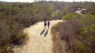 Mother hiking with her adult daughter, aerial follow shot video