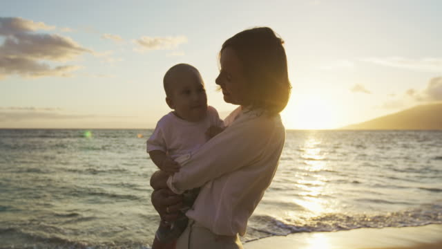 Mother holding baby son walking on the beach video