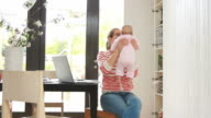 Mother holding baby working from home on phone video