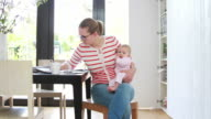 Mother holding baby working from home video