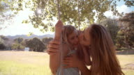Mother hugging her daughter on swing in park slow motion video