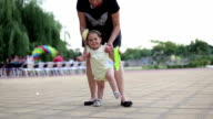 mother is learning her one year old baby to walk, while is she carrying frisbee video