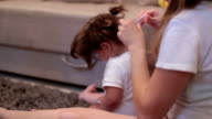 Mother is making pony tail on her baby's hair, while baby is using the phone video