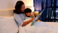 Mother is reading a book with her son video