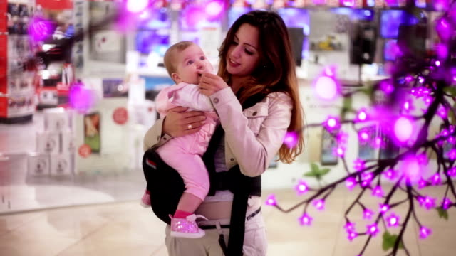 Mother kisses her baby in Shopping Mall video