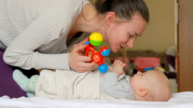 Mother kissing her baby and playing with rattles. video