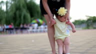 mother learning her one year old baby girl to walk , but she wants to be held video