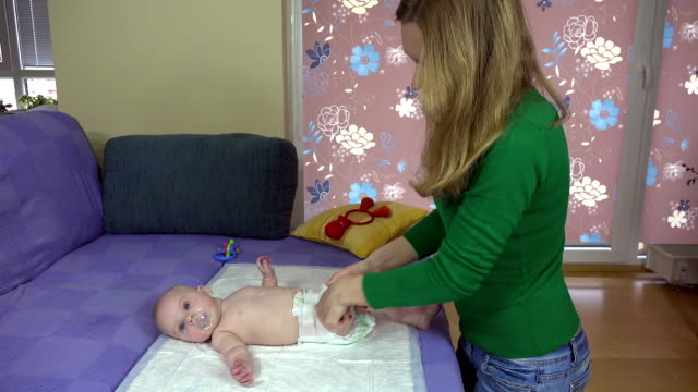 Mother massage her little baby daughter legs on bed video